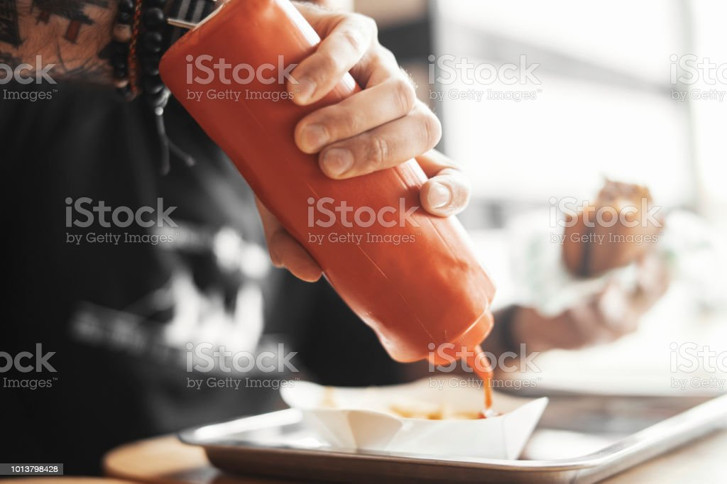 Young Bearded Hipster Man Pours Ketchup On French Fries