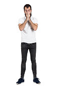 Young bearded hipster sneezing and covering his face with hands. Full body length portrait isolated over white studio background.