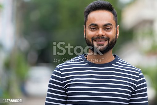 Portrait of young bearded Indian man in the streets outdoors