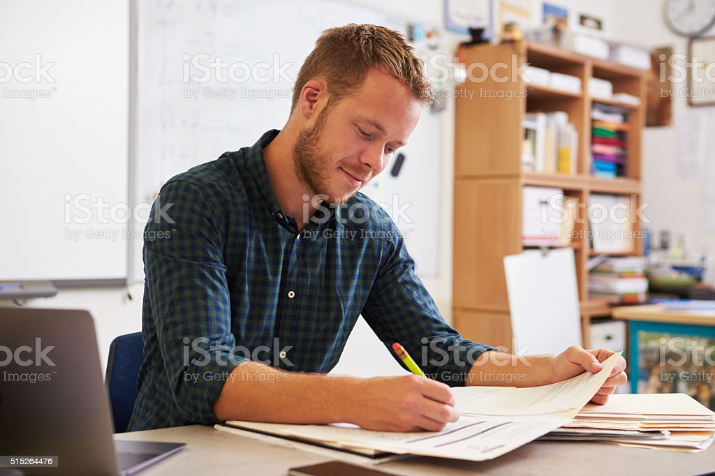 Young bearded male teacher at desk marking students' work stock photo