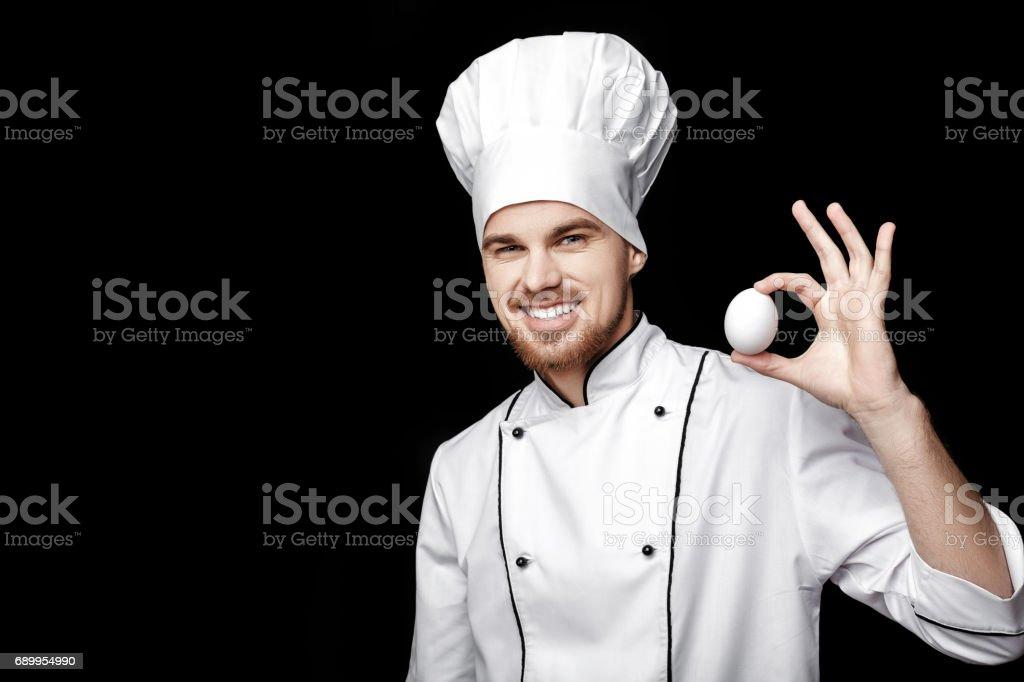 Barbu de jeune chef de l'homme en blanc uniformes cales oeuf sur fond noir - Photo