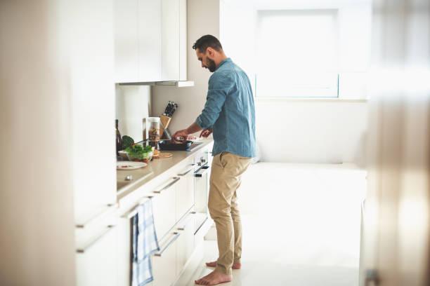 아늑한 부엌에서 저녁 식사를 요리 하는 젊은 수염 남자 - 요리하기 식품 상태 뉴스 사진 이미지