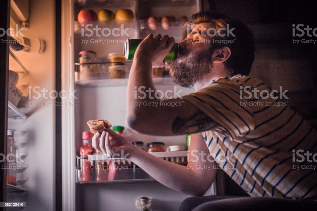 Young bearded man having a beer and late night snack in front of the refrigerator stock photo