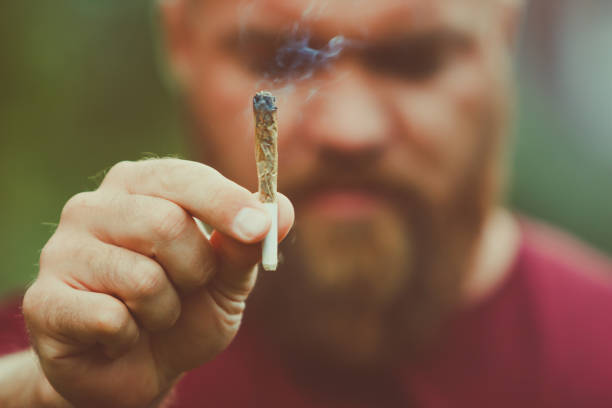 Young bearded man holding a smoking marijuana joint - legalization medical cannabis concept - smoke is coming out of the weed or hashish cigarette