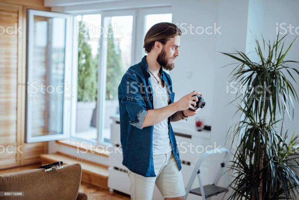 Jovem barbudo homem segurando a câmera polaroid e caminhando em direção a janela - foto de acervo