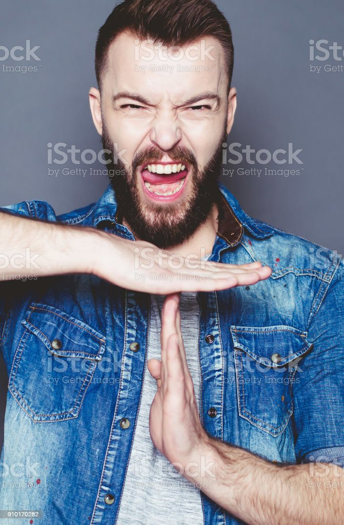 A young bearded man in a denim shirt much screaming with eyes closed stock photo