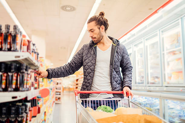 Young Bearded Man In A Supermarket. Young bearded man in groceries shopping. He is standing and reading nutrition label on product. Location released. man bun stock pictures, royalty-free photos & images