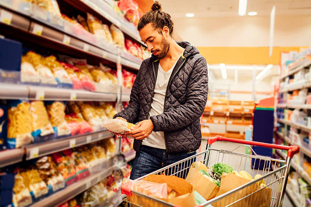 Young Bearded Man In A Supermarket. Young bearded man in groceries shopping. He is choosing pasta and reading nutrition label on product. Location released. man bun stock pictures, royalty-free photos & images