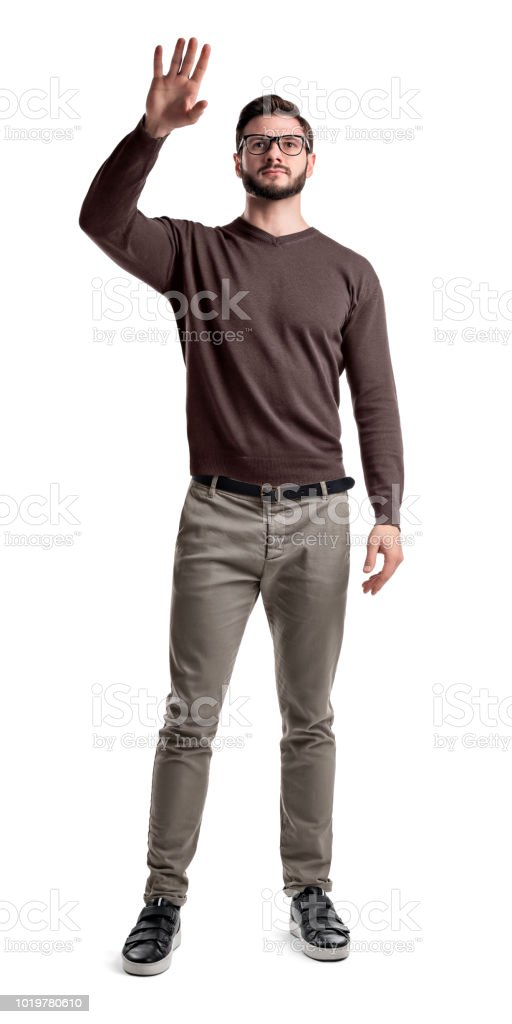 A Young Bearded Man In Cargo Pants Holds Up His Hand To