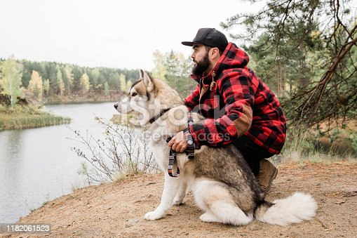508014973 istock photo Young bearded man in casualwear embracing husky dog during chill 1182061523