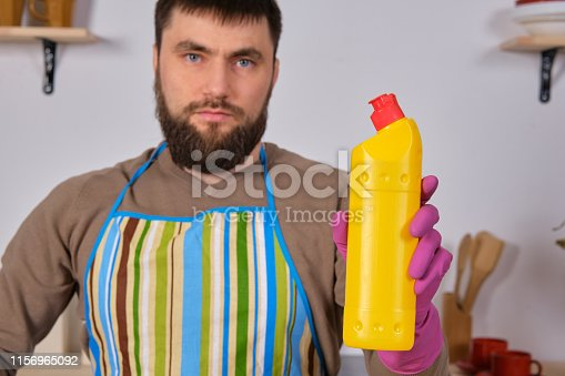 istock Young bearded man in kitchen makes advertising. He promotes detergent, holding it in one hand and shows at camera 1156965092
