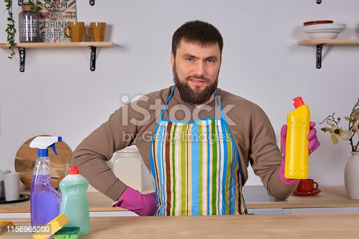 istock Young bearded man in kitchen makes advertising. He promotes detergent, holding it in one hand and shows at camera 1156965200
