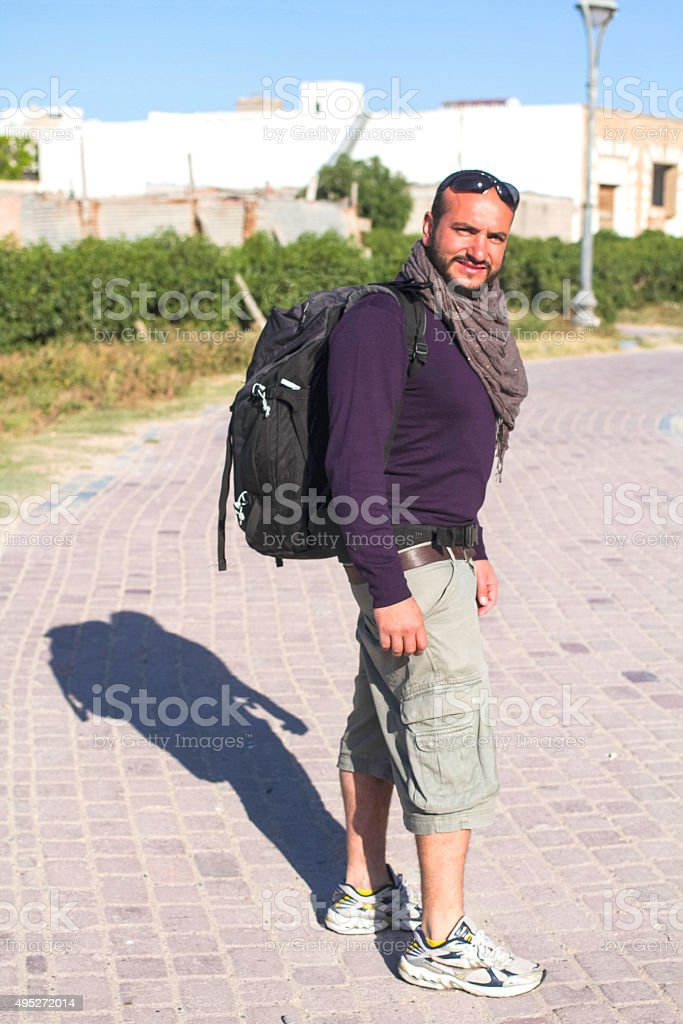 Young bearded man in travel. Vertical. Backpacker. stock photo