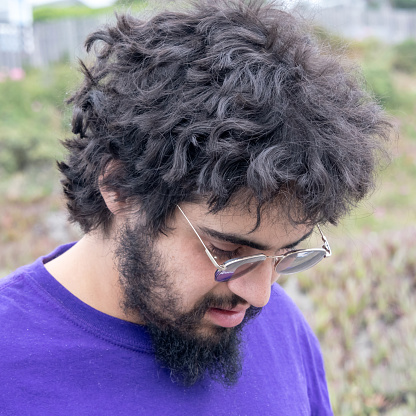 Young bearded man looking down