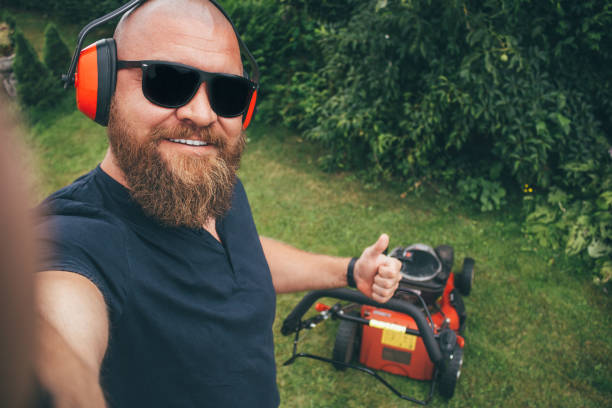 Young bearded man making selfie while mows the lawn, cutting down the grass in the garden picture of young man making selfie with lawn mower mowing stock pictures, royalty-free photos & images