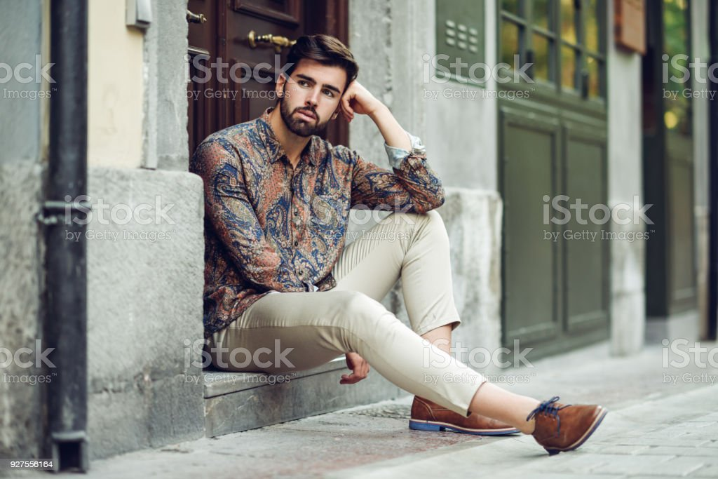 Young bearded man, model of fashion, sitting in an urban step wearing casual clothes. stock photo