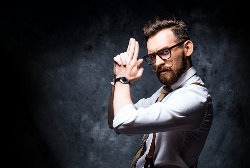 istock Young bearded man posing with a finger gun 532871088