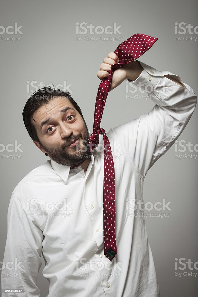 Young bearded man pretending to hang himself with a tie royalty-free stock photo