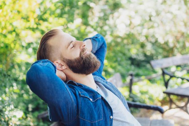 jovem barbudo homem relaxante num banco do parque - banco assento - fotografias e filmes do acervo