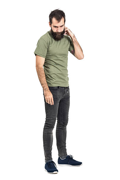 Young bearded man scratching head looking down side view Young bearded man scratching head looking down side view. Full body length portrait isolated over white studio background. men in tight jeans stock pictures, royalty-free photos & images