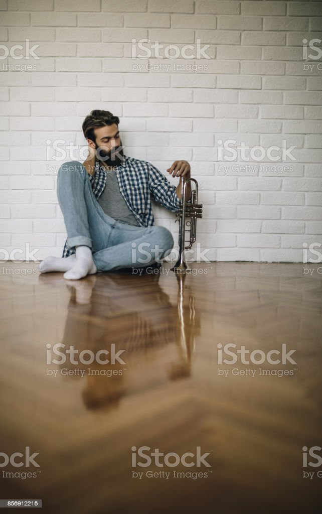 Young bearded man sitting on parquet floor with trumpet. stock photo