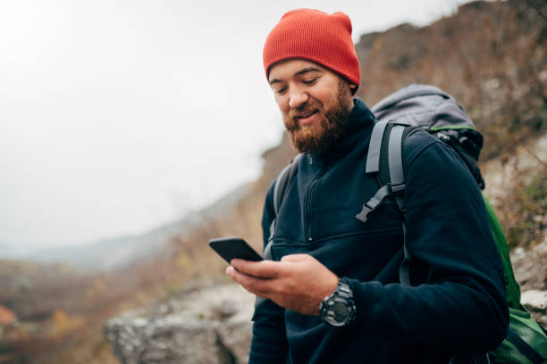 Young bearded man smiling and sending messages for his family from his cellphone, during hiking in mountains. Traveler bearded man in red hat using mobile phone application. Travel and lifestyle stock photo