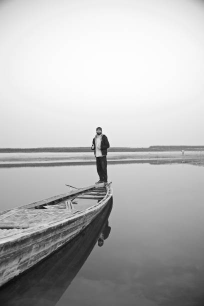 Young bearded man standing on a boat stock photo