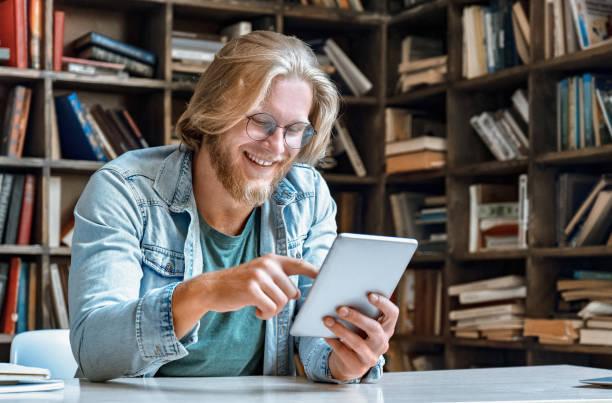 jonge bebaarde man student student student leraar bril kantoor huis bibliotheek bureau houden moderne tablet computer gebruik app surfen net sociale netwerk kijken video oproep glimlach tik touch screen kopieerruimte - e learning stockfoto's en -beelden