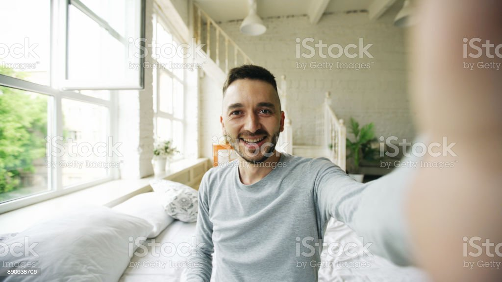 Young bearded man using tablet computer having video chat sitting in bed at home stock photo