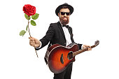 istock Young bearded man with an acoustic guitar holding a red rose 1155753213