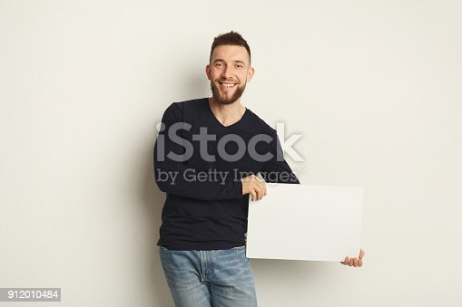 istock Young bearded man with blank white paper 912010484