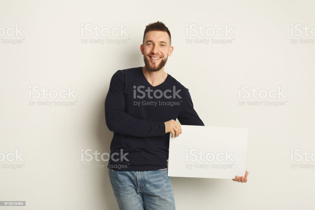 Young bearded man with blank white paper stock photo