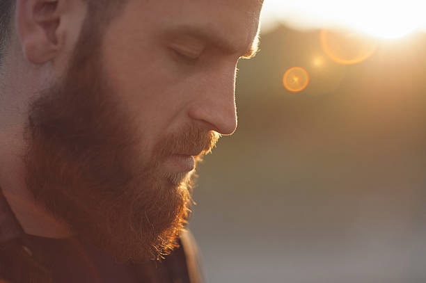 young bearded man with eyes closed - concentration stock photos and pictures
