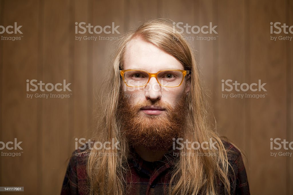 young bearded man with long hair and horn rimmed glasses stock photo