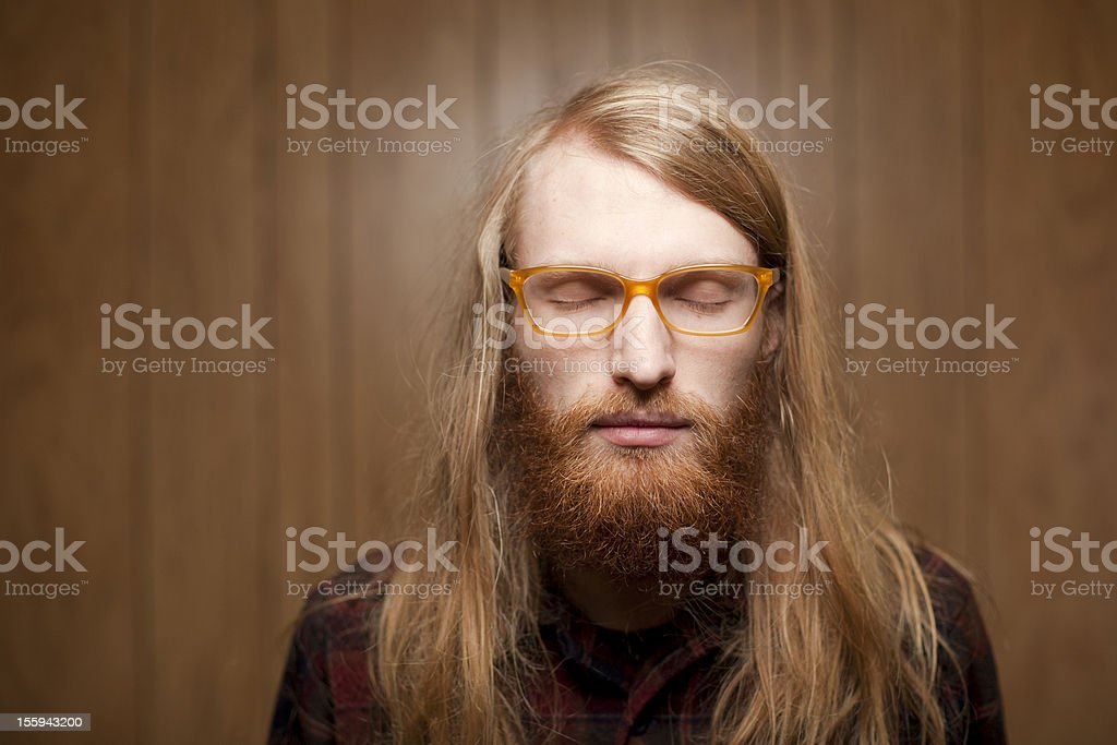 young bearded man with long hair closing his eyes stock photo