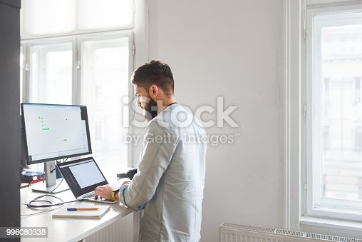 Young bearded male working on computer at his office