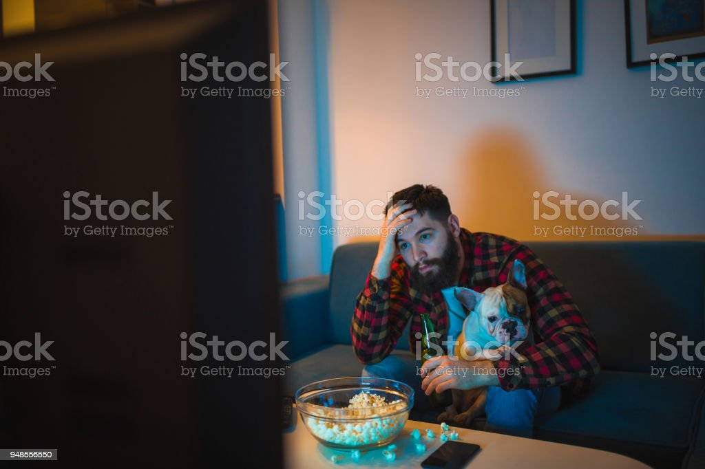 Young bearded men watching sport on television with his dog stock photo