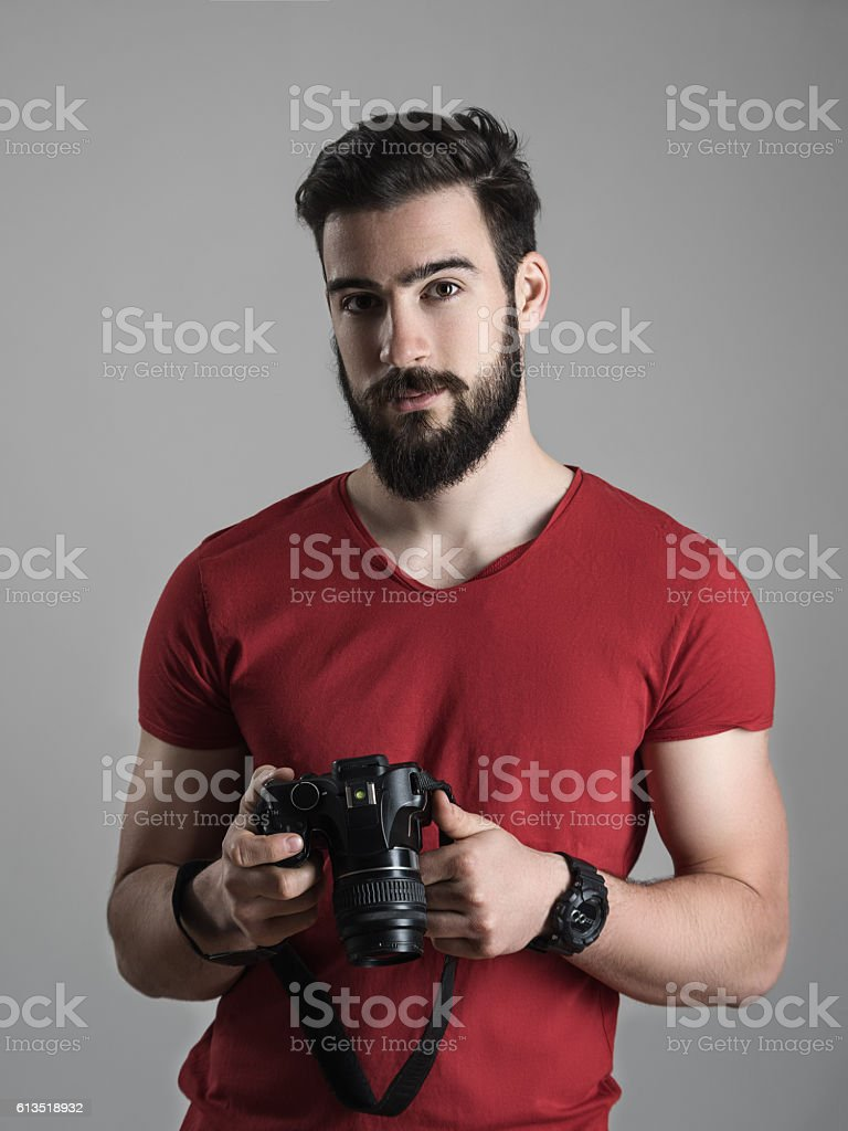 Young bearded photographer in red shirt holding dslr camera stock photo
