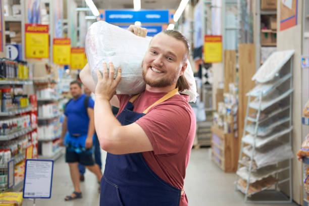 young bearded salesman carries a pack of plaster on his shoulder in counstruction store - materiał budowlany zdjęcia i obrazy z banku zdjęć