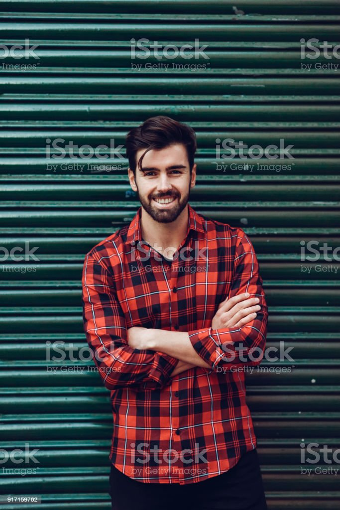 Young bearded smiling man wearing a plaid shirt with a green blind behind him. stock photo