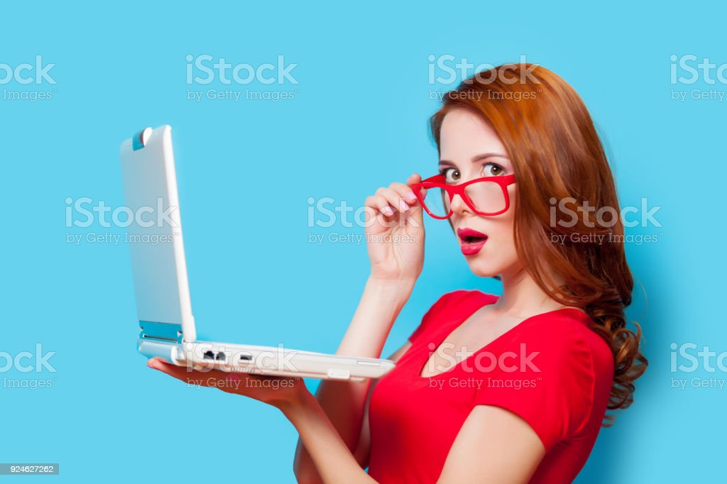 Young beautfiul redhead girl in eyeglasses with laptop computer stock photo