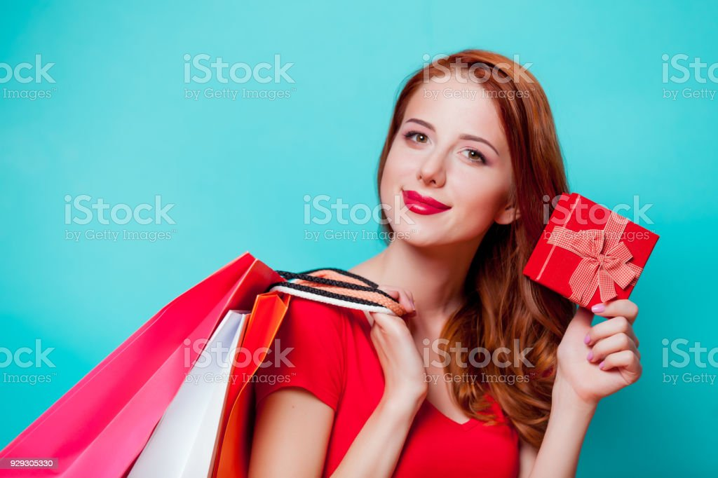 Young beautfiul redhead girl in eyeglasses with shopping bags stock photo