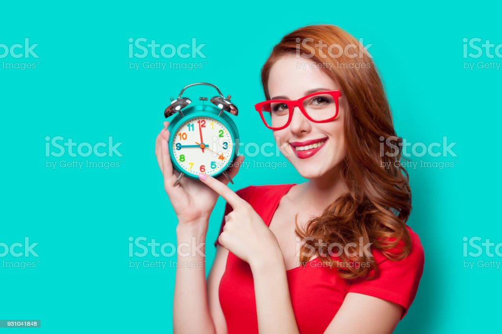 Young beautfiul redhead girl with alarm clock on minty background stock photo