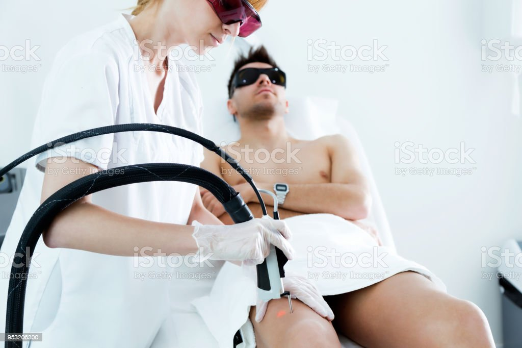 Young beautician removing legs hair with a laser to her client in the beauty salon. stock photo