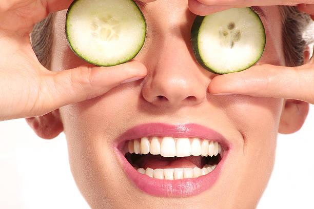 junge beautiflul lächeln mädchen anwendung einer gurken-beauty-behandlung - gurkenmaske stock-fotos und bilder