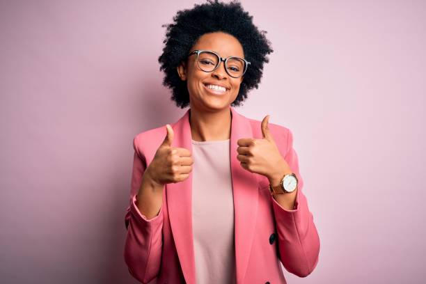 Young beautiful African American afro businesswoman with curly hair wearing pink jacket success sign doing positive gesture with hand, thumbs up smiling and happy. Cheerful expression and winner gesture. stock photo