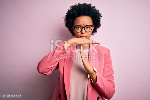 Young beautiful African American afro businesswoman with curly hair wearing pink jacket Doing time out gesture with hands, frustrated and serious face