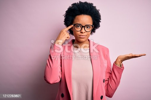 istock Young beautiful African American afro businesswoman with curly hair wearing pink jacket confused and annoyed with open palm showing copy space and pointing finger to forehead. Think about it. 1212263801