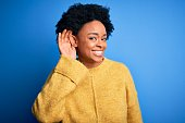 istock Young beautiful African American afro woman with curly hair wearing yellow casual sweater smiling with hand over ear listening an hearing to rumor or gossip. Deafness concept. 1212261950