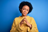 istock Young beautiful African American afro woman with curly hair wearing yellow casual sweater Hands together and fingers crossed smiling relaxed and cheerful. Success and optimistic 1212261974